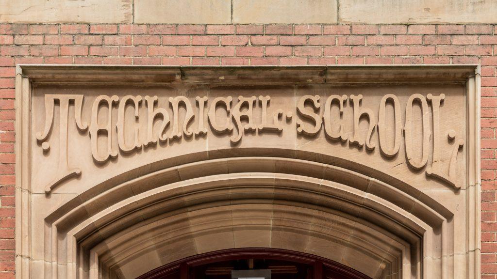 """Sandfärgad portal med skriften """"Technical school"""" uthuggen i sten"""