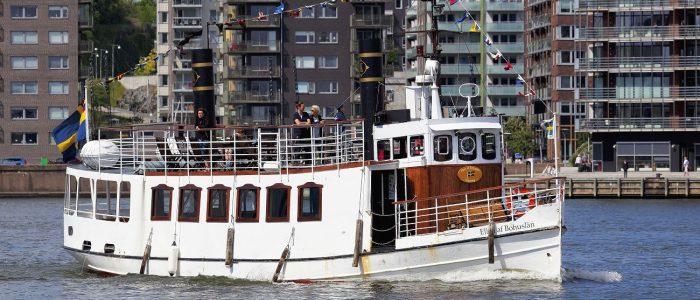 Det via fartyget M/S Ellen af Bohuslän är på väg till höger i bilden. I bakgrunden är det höghus med balkonger ut mot vattnet.